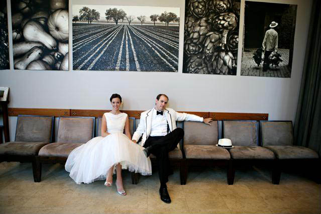 Bride and groom sitting in front of art